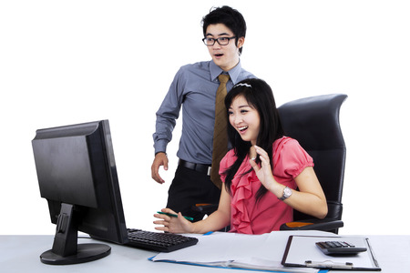 calculator chinese: Two young business people surprised with computer on the desk Stock Photo
