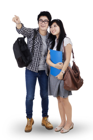 Happy trendy college students with bags and books, pointing at copy space photo