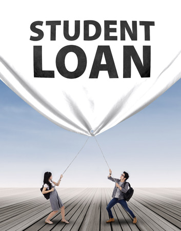 education loan: Young couple pulling a big banner of student loan Stock Photo