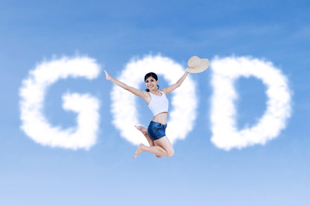 word of god: Religious  woman is jumping in front of the cloud word which says GOD