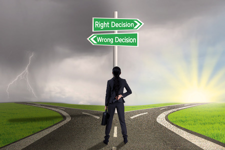 right vs wrong: Businesswoman looking at sign of right vs wrong decision on highway