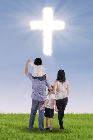 familia cristiana: Familia cristiana que se divierten en campo verde con el s�mbolo de la cruz