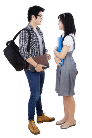Couple students with books and bags standing on white background photo