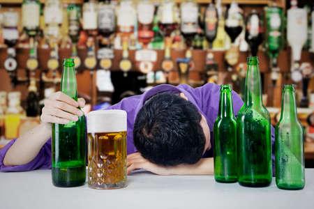 alcoholismo: Hombre borracho durmiendo en el bar, con una botella de cerveza en la mano