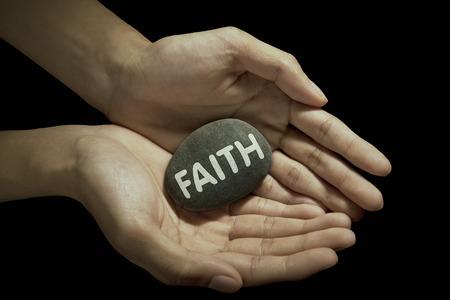 Hand holding faith word on stone