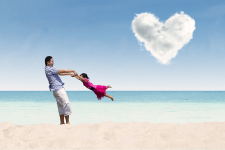 under heart: Father lifting his daughter under heart cloud Stock Photo