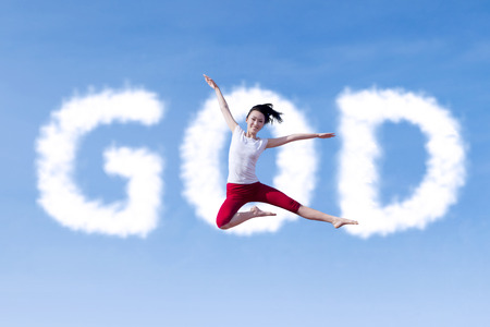 Beautiful girl is jumping with clouds shaped of God photo