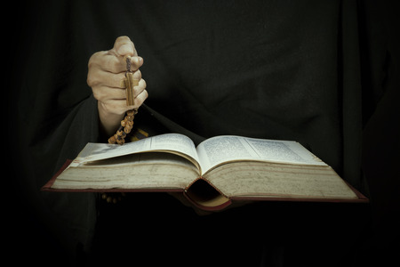 Man hands holding bible and rosary during prayer photo