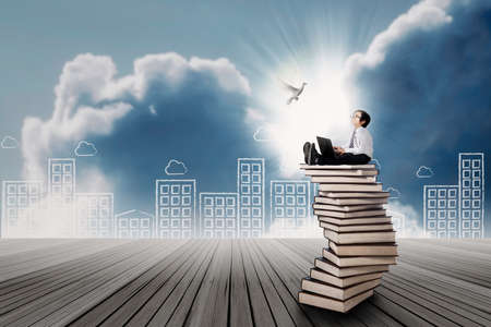 hispanic boy: Concept of Kid with bright future. Asian boy looking at dove and using a laptop sitting on stack of books Stock Photo