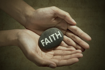 Man holding faith word on stone in palm photo