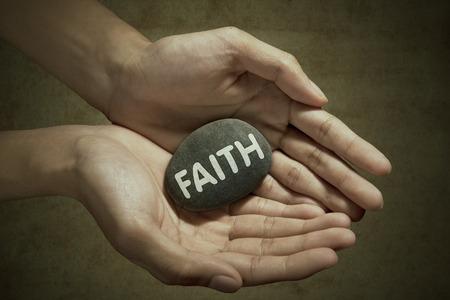 trust god: Man holding faith word on stone in palm Stock Photo
