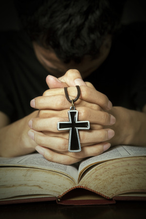 jesus hands: Man praying to God with bible and rosary on his hands