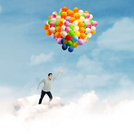 Young man flying with colorful balloons in blue sky photo