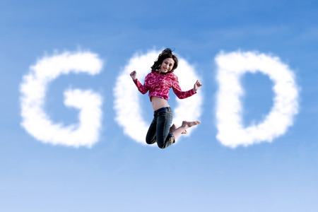 Happy religious woman jumping with the word god shaped cloud photo
