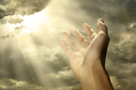 Hand reaching for a ray of light on the sky Stock Photo