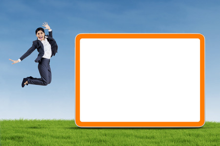 Happy businesswoman is jumping with blank board on the meadow photo