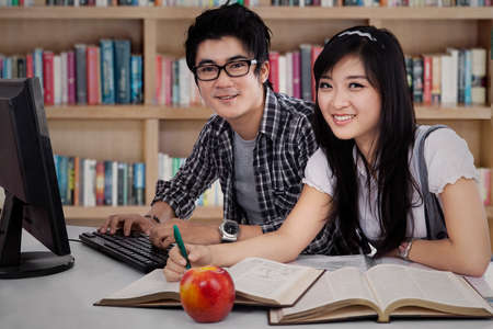 Two asian college students studying together at library photo
