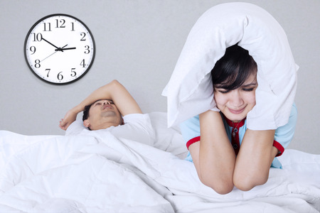 Husband snoring in sleep and wife suffering on a bed