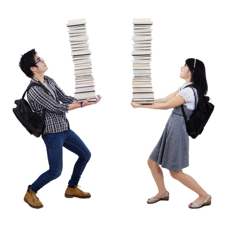 Young couple carrying a pile of books isolated on white background photo