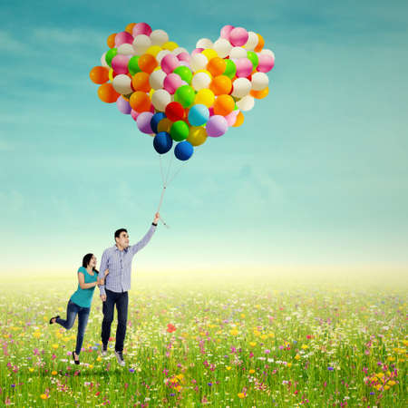 Young couple with colorful balloons at the park photo
