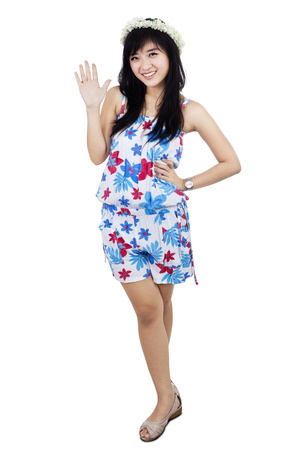 Portrait of attractive beautiful young woman wearing crown of flower is waving her hand photo