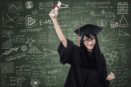 high school graduation: Woman in graduation gown expressing success in front of blackboard Stock Photo