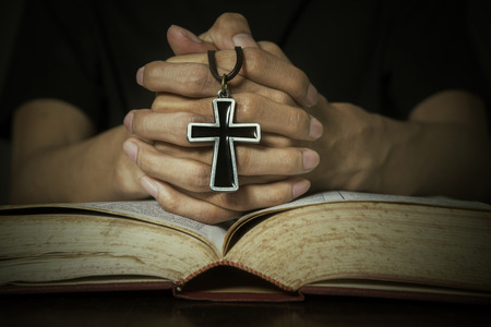clasped: The holy bible with rosary on a man hand