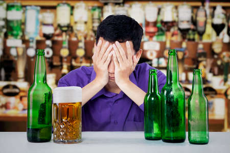 boozer: Sad alcoholic man with beer bottles and glass on the table in a bar