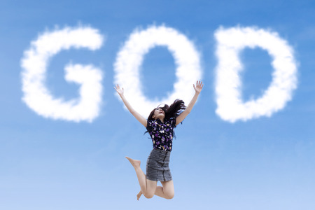 Excoted religious woman jumping with the word of God shaped clouds photo