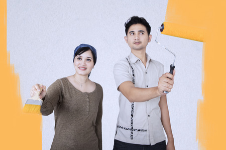 Young couple is painting in yellow color the wall of their new home photo