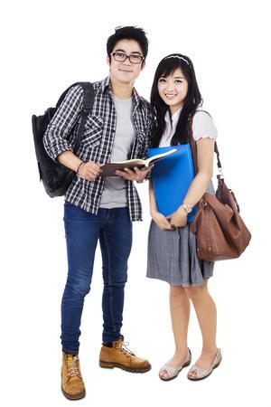 勉強と笑みを浮かべて、白い背景で隔離のカップル学生