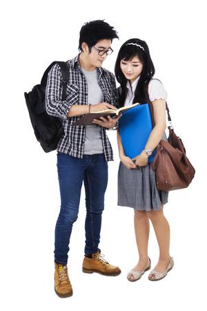 白い背景で隔離の本を読んでカップル学生 写真素材