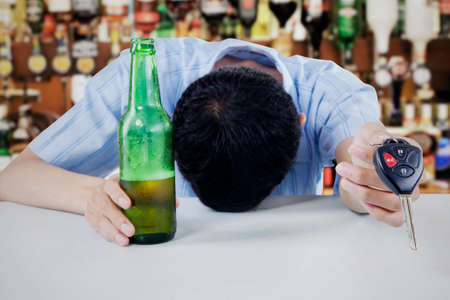 Young drunk man sleeping in the bar, with bottle of whiskey and key in his hand photo