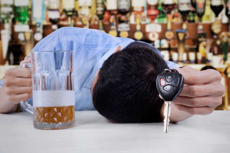 Drunk young man giving a key and sleeping in the bar photo