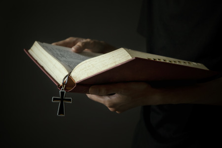Hands of man holding holy bible and wooden rosary photo