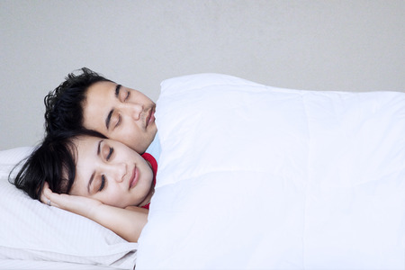 Young couple sleeping together in their bed photo