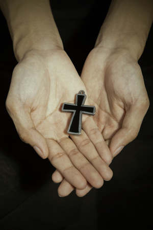 hallelujah: Man hands holding a cross on dark background