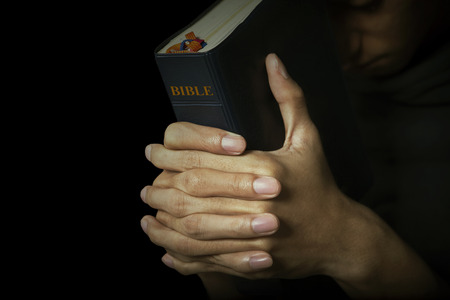 Man holds his bible with interlocked fingers to pray