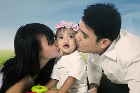 Happy mother and father kissing their daughter in the park photo