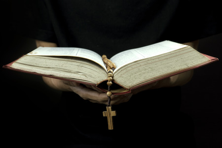 Close up of priest reading the holy bible with rosary photo