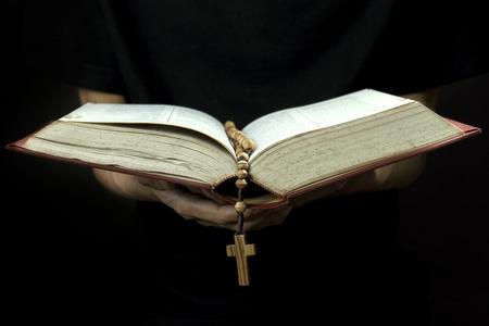 Close-up van de priester, het lezen van de Bijbel met rozenkrans Stockfoto