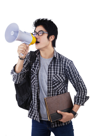 College student shouting through megaphone isolated on white background photo