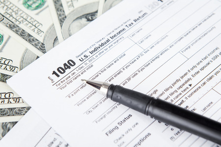 Close up of tax forms with dollar bills and pen photo