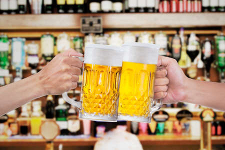 brewery: Two human hands toast with glasses of beer at the bar Stock Photo