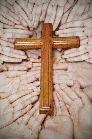 Human hands holding wooden cross symbol photo