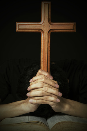Worshipper praying with cross and a holy bible photo