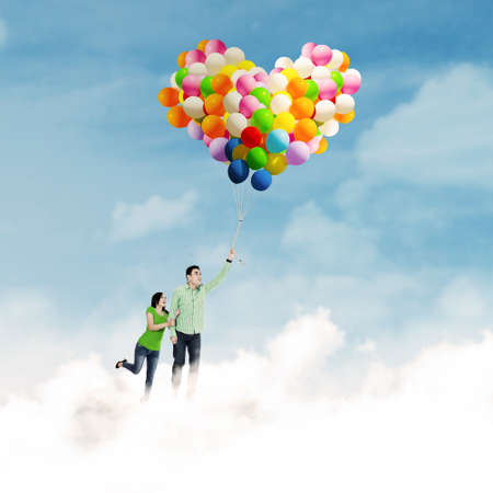 Romantic young couple holding colorful balloons on the clouds photo