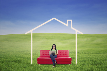 Asian female is working on laptop on red sofa with dream house picture outdoor photo