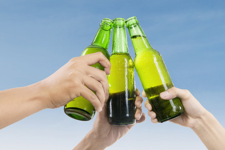 Closeup of hands toasting with bottles of beer photo