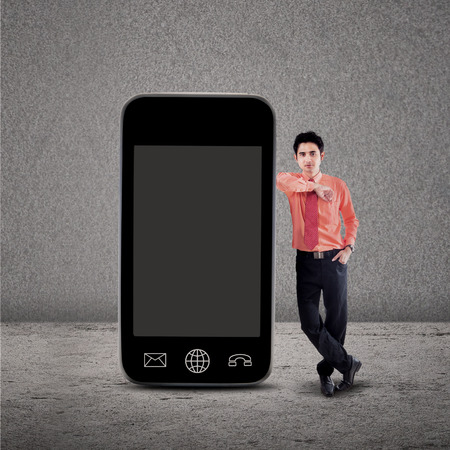 Businessman standing next to smartphone on grey background photo